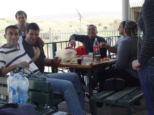 קבוצה יושבת לאכול בשמש