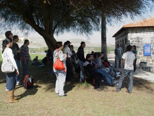 קבוצה נהנת בדשא הירוק תחת צל